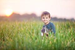 Νέο αγόρι με ένα κουνέλι κατοικίδιων ζώων σε έναν τομέα Στοκ εικόνα με δικαίωμα ελεύθερης χρήσης