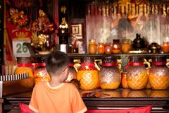 Νέο αγόρι παραγωγής που προσεύχεται για την καλές τύχη και την ευτυχία σε έναν κινεζικό ναό στοκ εικόνες