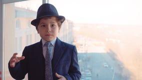 Νέο αγόρι πορτρέτου στο επιχειρησιακό κοστούμι, το δεσμό και το καπέλο στο υπόβαθρο παραθύρων στην αρχή απόθεμα βίντεο