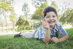 Νέο αγόρι που απολαμβάνει το Lollipop του που βάζει υπαίθρια στη χλόη Στοκ εικόνες με δικαίωμα ελεύθερης χρήσης