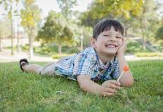Νέο αγόρι που απολαμβάνει το Lollipop του που βάζει υπαίθρια στη χλόη Στοκ Εικόνα