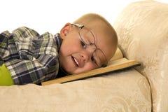 Νέο αγόρι που βάζει ένα βιβλίο με τα γυαλιά επάνω Στοκ Φωτογραφία