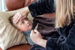 Νέο αγόρι που βρίσκεται σε έναν καναπέ που φαίνεται άρρωστο ενώ η μητέρα ελέγχει τη θερμοκρασία στοκ φωτογραφία