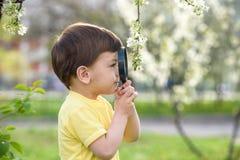 Νέο αγόρι που ερευνά τη φύση σε ένα λιβάδι με την ενίσχυση - γυαλί Στοκ φωτογραφία με δικαίωμα ελεύθερης χρήσης