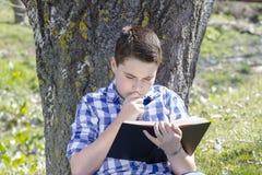 Νέο αγόρι που διαβάζει ένα βιβλίο στα ξύλα με το ρηχό βάθος του τομέα Στοκ Εικόνες