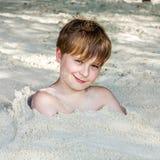 Νέο αγόρι που καλύπτεται από τη λεπτή άμμο στην παραλία Στοκ Φωτογραφία