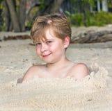 Νέο αγόρι που καλύπτεται από τη λεπτή άμμο Στοκ φωτογραφία με δικαίωμα ελεύθερης χρήσης