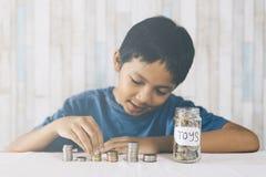 Νέο αγόρι που μετρά τα νομίσματα/την αποταμίευσή του για να αγοράσει τα παιχνίδια ονείρου Στοκ Εικόνες