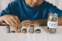 Νέο αγόρι που μετρά τα νομίσματα/την αποταμίευσή του για να αγοράσει τα παιχνίδια ονείρου Στοκ φωτογραφίες με δικαίωμα ελεύθερης χρήσης