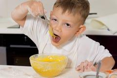 Νέο αγόρι που παίρνει ένα γούστο του μίγματος κέικ Στοκ Εικόνες