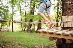 Νέο αγόρι που περνά τη διαδρομή καλωδίων μεταξύ των δέντρων, ακραίος αθλητισμός στο πάρκο περιπέτειας στοκ φωτογραφία με δικαίωμα ελεύθερης χρήσης