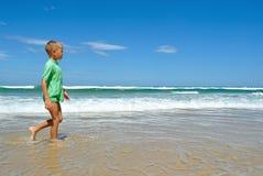 Νέο αγόρι που περπατά κατά μήκος της άκρης νερών Στοκ Εικόνες