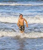 Νέο αγόρι που τρέχει μέσω του νερού στην παραλία Στοκ φωτογραφία με δικαίωμα ελεύθερης χρήσης