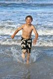 Νέο αγόρι που τρέχει μέσω του νερού Στοκ Φωτογραφία