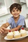 Νέο αγόρι που τρώει τα κέικ στην κουζίνα Στοκ Εικόνες