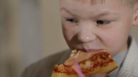Νέο αγόρι που τρώει την πίτσα στο εστιατόριο απόθεμα βίντεο