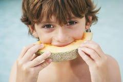 Νέο αγόρι που τρώει τη φέτα του πεπονιού Στοκ εικόνα με δικαίωμα ελεύθερης χρήσης