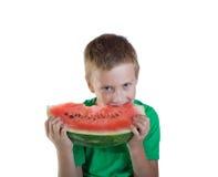 Νέο αγόρι που τρώει το κόκκινο πεπόνι Στοκ εικόνα με δικαίωμα ελεύθερης χρήσης