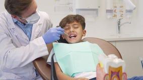 Νέο αγόρι που φαίνεται φοβησμένο, έχοντας τα δόντια του που εξετάζονται από τον ώριμο οδοντίατρο απόθεμα βίντεο