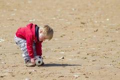 Νέο αγόρι στην παραλία που τοποθετεί τη σφαίρα για ένα ελεύθερο λάκτισμα στοκ εικόνες