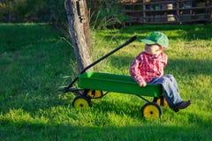 Νέο αγόρι στο βαγόνι εμπορευμάτων Childs σε ένα λιβάδι Στοκ Φωτογραφία
