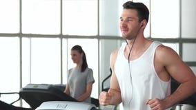 Νέο αθλητικό άτομο που τρέχει treadmill απόθεμα βίντεο