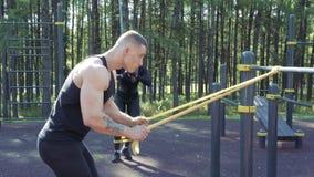 Νέο αθλητικό ζεύγος που κάνει την άσκηση με τις ελαστικές ζώνες υπαίθρια φιλμ μικρού μήκους