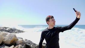Νέο αθλητικό κατάλληλο καυκάσιο άτομο στη μαύρη λήψη selfies και το χαμόγελο στεμένος στη δύσκολη παραλία με το χτύπημα κυμάτων κ απόθεμα βίντεο