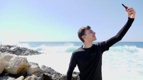 Νέο αθλητικό κατάλληλο καυκάσιο άτομο στη μαύρη λήψη selfies και το χαμόγελο στεμένος στη δύσκολη παραλία με το χτύπημα κυμάτων κ φιλμ μικρού μήκους