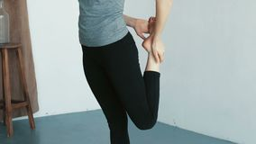 Νέο αθλητικό κορίτσι που τεντώνει τα πόδια της πριν από την άσκηση ικανότητας και το μάθημα χορού σε σε αργή κίνηση φιλμ μικρού μήκους