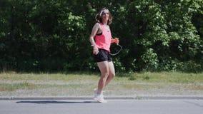 Νέο αθλητικό κορίτσι στα ακουστικά που χορεύουν και που γύρω Χαριτωμένο κορίτσι που χαμογελά και που γελά στο πάρκο Ελκυστικό νέο απόθεμα βίντεο