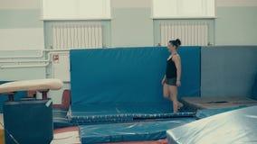 Νέο αθλητικό κορίτσι στη γυμναστική που κάνει ένα πίσω κτύπημα απόθεμα βίντεο