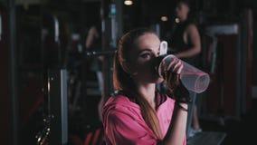 Νέο αθλητικό πόσιμο νερό γυναικών στη γυμναστική φιλμ μικρού μήκους