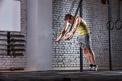 Νέο αθλητικό άτομο στη sportwear κατάρτιση στη διαγώνια κατάλληλη γυμναστική με τα δαχτυλίδια ενάντια στο τουβλότοιχο Στοκ Εικόνες