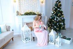 Νέο αμερικανικό μωρό και συνεδρίαση εκμετάλλευσης μητέρων στον καναπέ κοντά στα φανάρια, την εστία και το χριστουγεννιάτικο δέντρ Στοκ Εικόνες