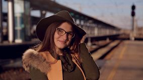 Νέο αμερικανικό πορτρέτο γυναικών υπαίθρια Όμορφη φυσική γυναίκα με τα γυαλιά και ένα καπέλο που χαμογελά και που εξετάζει τη κάμ απόθεμα βίντεο