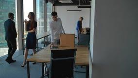 Νέο ανοίγοντας κιβώτιο υπαλλήλων με τα έγγραφα και τον εξοπλισμό Οι συνάδελφοί του που περπατούν πλησίον στο σύγχρονο γραφείο απόθεμα βίντεο