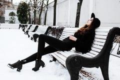 Νέο αρκετά σύγχρονο κορίτσι hipster που περιμένει στον πάγκο στο πάρκο χειμερινού χιονιού μόνο, έννοια ανθρώπων τρόπου ζωής Στοκ φωτογραφία με δικαίωμα ελεύθερης χρήσης