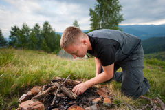 Νέο αρσενικό ανάβοντας καυσόξυλο οδοιπόρων στο λόφο με τη σκηνή Στοκ Φωτογραφία