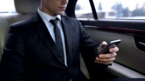 Νέο αρσενικό κοστουμιών στο smartphone οδηγώντας στο προσωπικό επιχειρησιακό αυτοκίνητο στοκ εικόνες με δικαίωμα ελεύθερης χρήσης