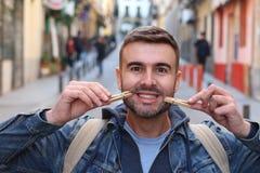 Νέο αρσενικό που επινοεί ένα χαμόγελο με τα clothespins στοκ εικόνες με δικαίωμα ελεύθερης χρήσης