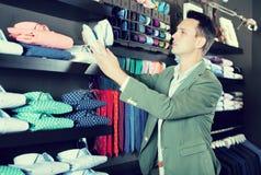 Νέο αρσενικό που επιλέγει το νέο πουκάμισο στο αρσενικό κατάστημα Στοκ Εικόνες