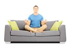 Νέο αρσενικό που κάθεται σε έναν καναπέ Στοκ εικόνα με δικαίωμα ελεύθερης χρήσης