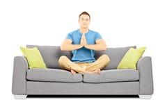 Νέο αρσενικό που κάθεται σε έναν καναπέ Στοκ Φωτογραφία
