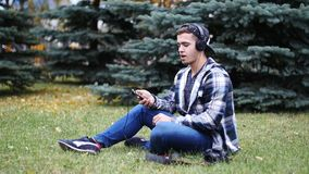 Νέο αρσενικό στα ακουστικά που κάθεται στη χλόη και το δέντρο, μουσική ακούσματος απόθεμα βίντεο