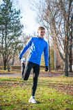 Νέο αρσενικό τέντωμα δρομέων στο πάρκο το κρύο ηλιόλουστο πρωί φθινοπώρου Υγιής έννοια τρόπου ζωής και αθλητισμού Στοκ Εικόνα