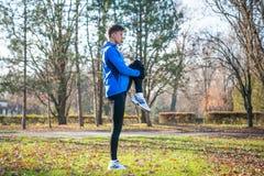Νέο αρσενικό τέντωμα δρομέων στο πάρκο το κρύο ηλιόλουστο πρωί φθινοπώρου Υγιής έννοια τρόπου ζωής και αθλητισμού Στοκ εικόνες με δικαίωμα ελεύθερης χρήσης