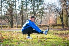 Νέο αρσενικό τέντωμα δρομέων στο πάρκο το κρύο ηλιόλουστο πρωί φθινοπώρου Υγιής έννοια τρόπου ζωής και αθλητισμού Στοκ Εικόνες