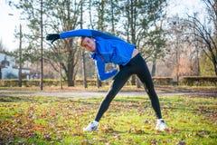 Νέο αρσενικό τέντωμα δρομέων στο πάρκο το κρύο ηλιόλουστο πρωί φθινοπώρου Υγιής έννοια τρόπου ζωής και αθλητισμού Στοκ φωτογραφία με δικαίωμα ελεύθερης χρήσης