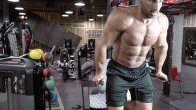 Νέο αρσενικό bodybuilder που κάνει ένα workout στη γυμναστική φιλμ μικρού μήκους